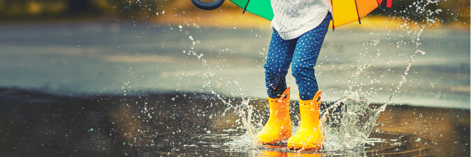 little girl in bright yellow wellies jumping in a puddle