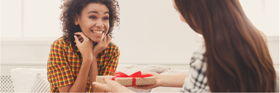 girl receiving a gift from friend