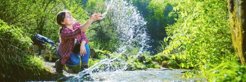 woman playing at a riverside